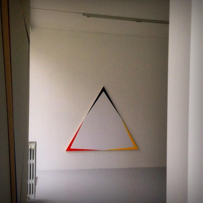 Grande toile triangulaire vue à travers la porte d'entrée de la galerie.